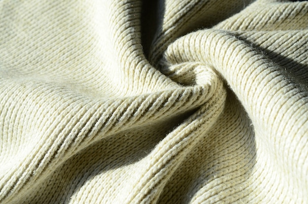 Fabric texture of a soft yellow knitted sweater. macro image of the structure of bindings in yarns