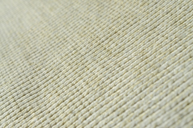 Fabric texture of a soft yellow knitted sweater.
