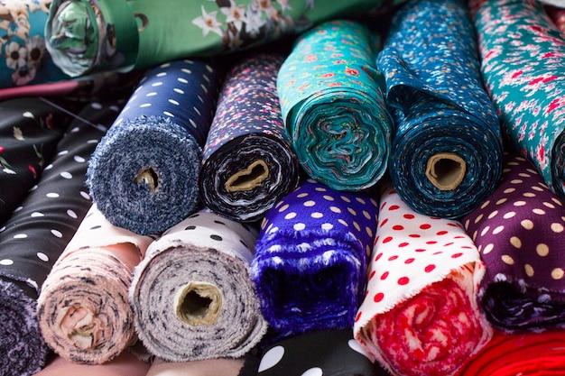 トビリシの市場で、店の棚にシルクと布を作り、多色で多くのパターンの巻きシルクを作ります