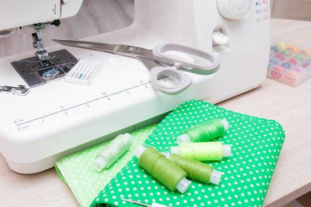 Ткани, швейная машина, ножницы и катушки с нитками на столе