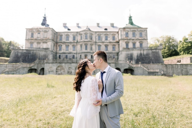 Fabulous asian wedding couple posing in front of an old medieval castle, hugging and kissing on a sunny day.