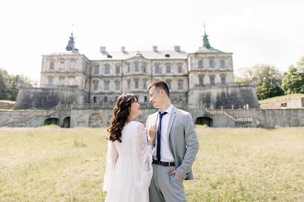 멋진 아시아 웨딩 커플 오래 된 중세 성 앞에서 포즈, 포옹과 화창한 날에 키스.