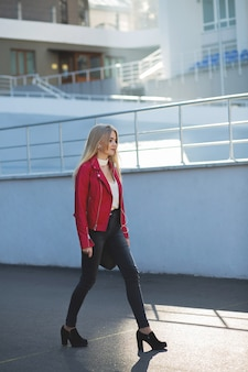 Fabulous blonde woman wearing red jacket walking down the street with sun light