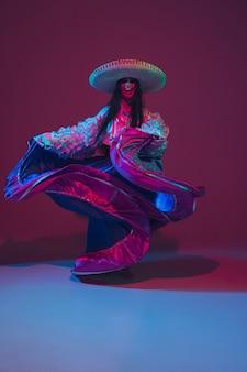네온 불빛에 보라색 벽에 멋진 cinco de mayo 여성 댄서.
