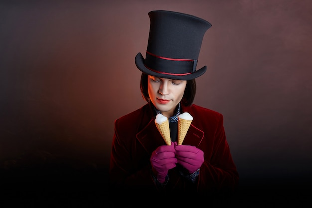 Fabulous circus man in a hat and a red suit posing in the smoke on a dark