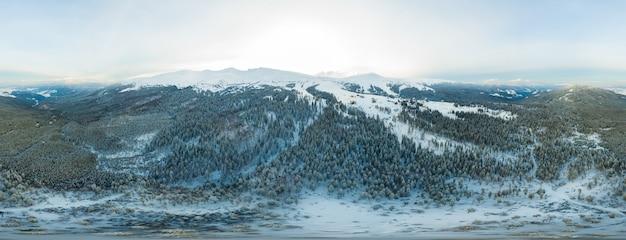 Сказочная вечерняя панорама с заснеженными горами и холмами с ярким солнцем и туманом морозным зимним вечером. красивая суровая концепция северной природы. copyspace