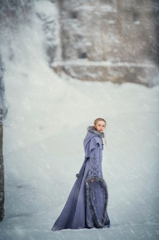 Fabulous girl elf walks near an ancient fortress and snow-covered winter nature