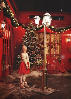 Сказочная маленькая девочка, стоящая на зимней улице на рождество, глядя на свет ребенок возле красного магазина