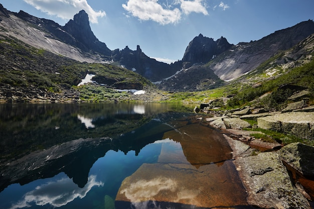 Fabulous mountains and lakes, travel and hiking, lush greenery and flowers around. thawed spring water from mountains