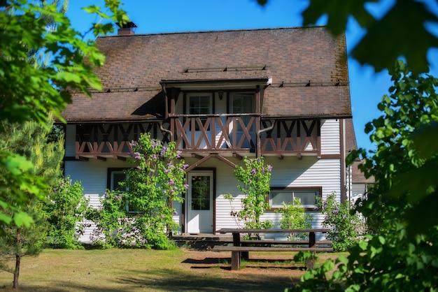 숲에 갈색 금속 지붕이 있는 멋진 소박한 흰색 집