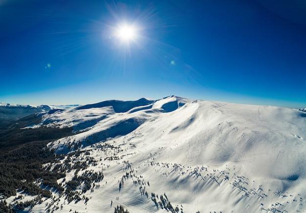 スキーリゾートにある雪に覆われた木々と日当たりの良い冬の斜面の素晴らしい景色