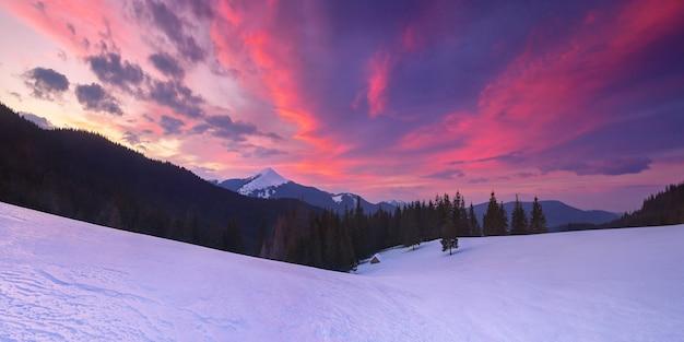 山の中に孤独な木造の家がある素晴らしい冬の風景。美しい雲とカラフルな夕日。雪をかぶった山頂