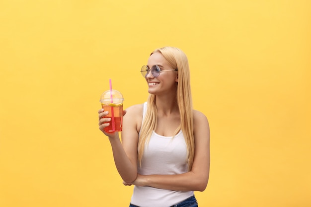 Fabulous woman in sunglasses wearing white t-shirt while holding glass of juice isolated over yellow background
