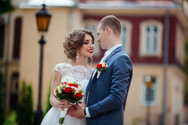 晴れた日に公園でポーズをとる素晴らしい若い結婚式のカップル