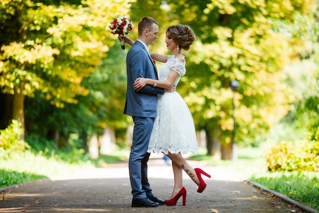 Fabulous young wedding couple posing in the park on the sunny day.