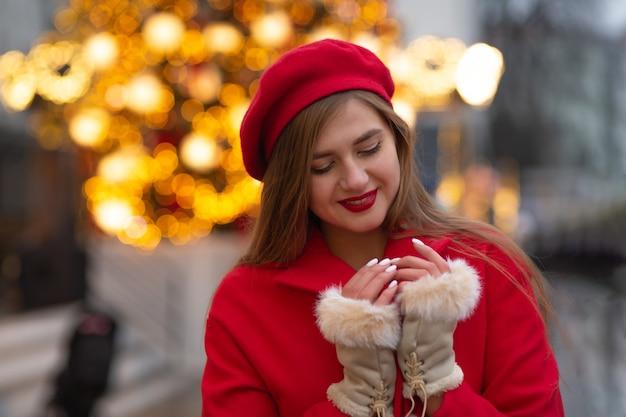 ストリートフェアを歩いている赤いコートを着た素晴らしい若い女性。空きスペース