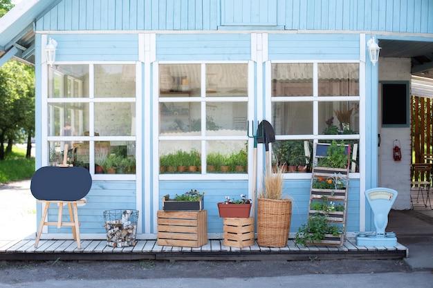 Фасад синего дома с садовыми инструментами