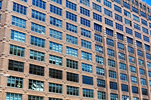 Facade of brick building with wooden windows.