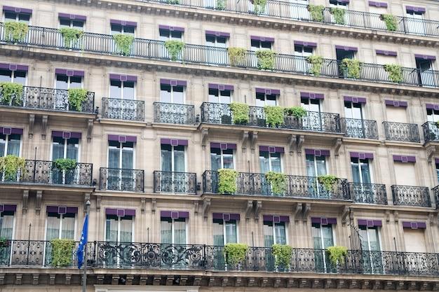 Фасадное здание с окнами и балконами. архитектурно-дизайнерская концепция. европейская архитектура. растения на балконе. роскошное архитектурное здание. путешествие и отдых. архитектурная концепция.