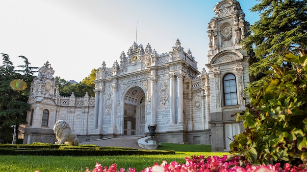 Facade of the dolmabahce palace with gardens full of greenery and flowers in front of it in istanbul, turkey