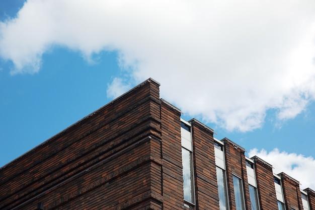 青い空、近代建築の上の近代的なオフィスビルのファサードの断片