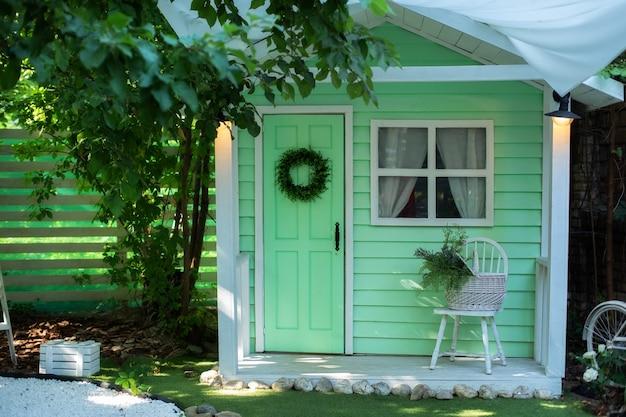 의자와 바구니 꽃이 있는 나무 현관이 있는 파사드 하우스