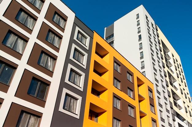 Фасад строящегося здания с окнами и цветной декоративной штукатуркой