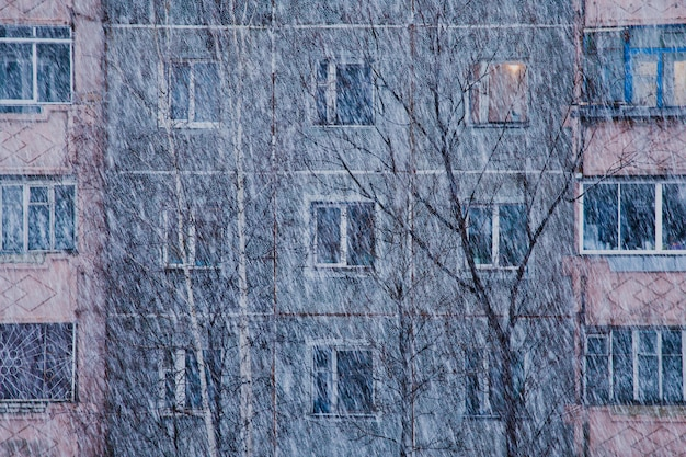 Фасад жилого дома зимой во время снегопада