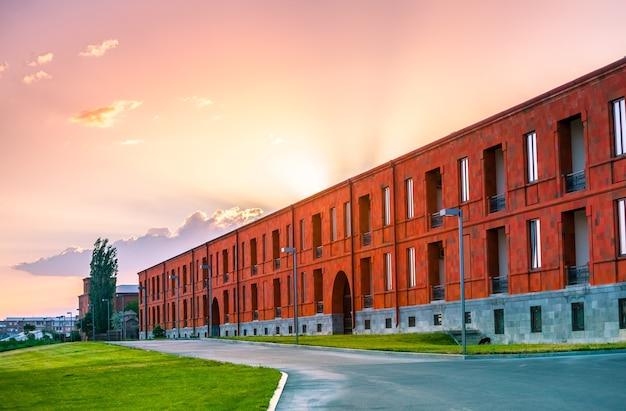 Фасад красивого красного современного здания на фоне закатного неба изучает армению