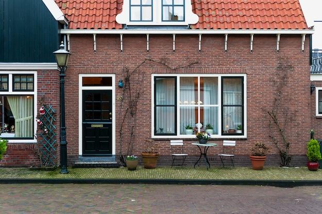 新年の装飾が施されたオランダの家のファサード。クリスマスのフォーレンダム村。オランダのれんが造りの家の近くの庭の家具。妖精の古い家。 Premium写真