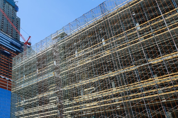 建物のファサードを覆う組立ラインの足場のための新しい商業用不動産の超高層ビル建設プロセスのファサード。