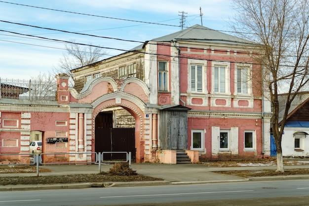 オレンブルク市の中庭ロシアへの木製のポーチとアーチ型の門のある古い建物のファサード