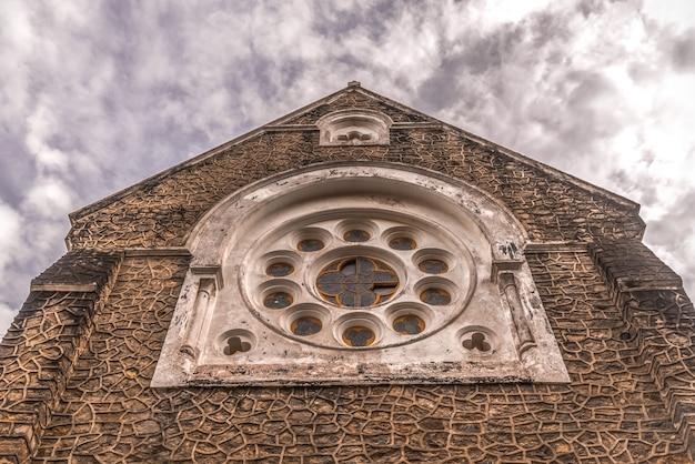 曇り空の背景のクローズアップとカトリック教会のファサード。