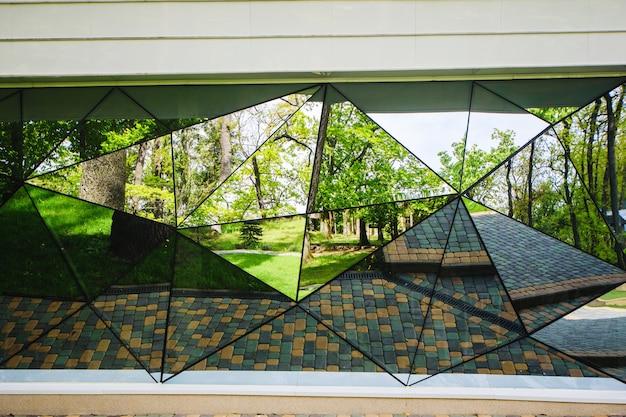 공원에 거울이 달린 창문이 있는 집의 정면.
