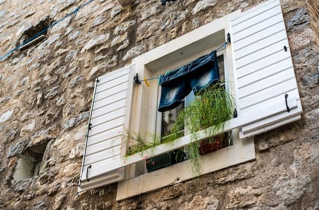구시 가지에 열린 창문이있는 벽의 외관