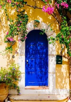 아름다운 분홍색 꽃을 가진 전통적인 그리스 건물의 외관. 그리스. 케 팔로 니아