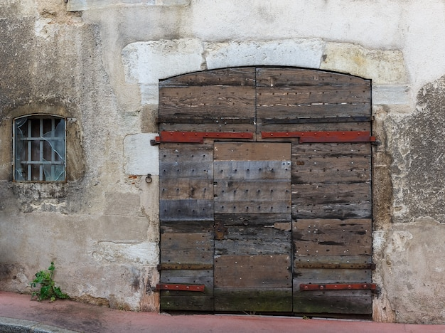 Facade of an old building with wooden gate and with a broken window