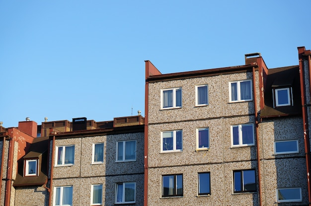 Facade of a row of apartment buildings against a clear blue sky