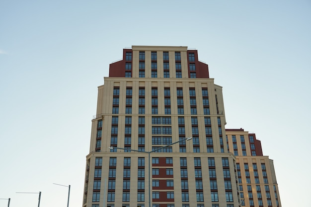 The facade of a tall building with windows against a clear sky.