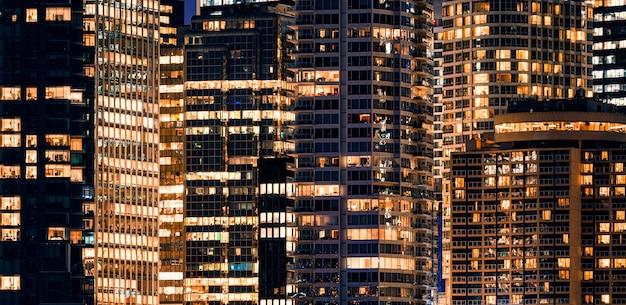 Facade windows of illuminated modern skyscraper with office building at night