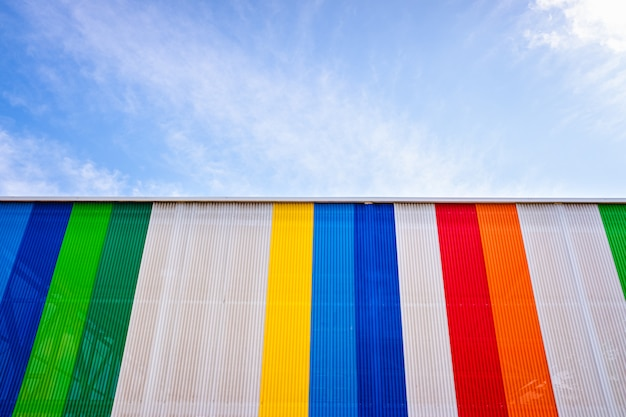 Facade with colored lines, against the blue sky in the background.