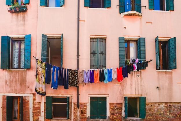 カラーウォッシュのファサード。服はベネチアの家の正面で乾かされます。