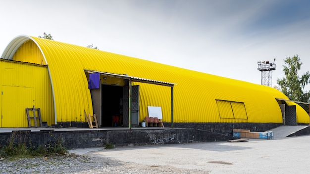 Facade of a yellow metal warehouse, commercial building for storage of goods.