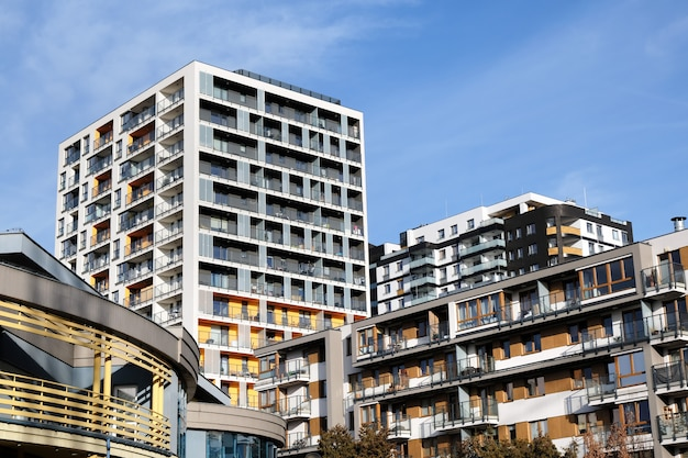 Facades of modern apartment buildings with balcony in contemporary residential district.