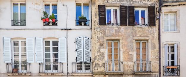유럽 지방 도시의 창문, 셔터 및 작은 발코니가있는 오래된 건물의 외관