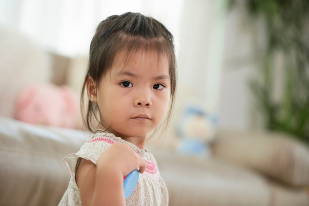Face of adorable little girl standing in living room and looking at camera