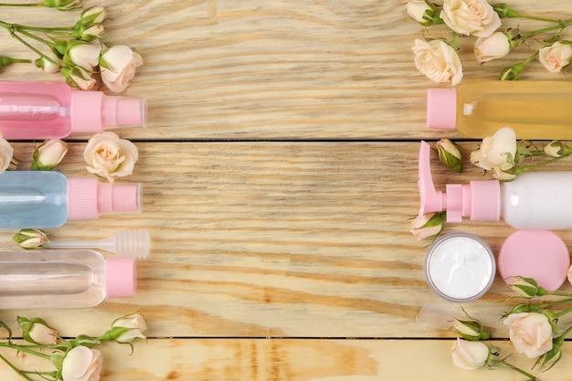 천연 나무 배경에 신선한 장미가 든 분홍색 병에 담긴 얼굴과 몸 화장품. 크림과 로션. 온천. 평면도. 텍스트를 위한 공간
