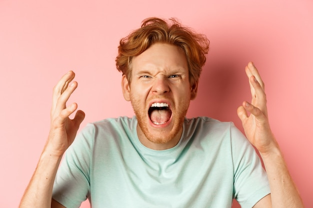 Face of angry redhead man shouting and shaking hands furious, staring outraged and cursing, express hatred and aggression, standing frustrated over pink background.