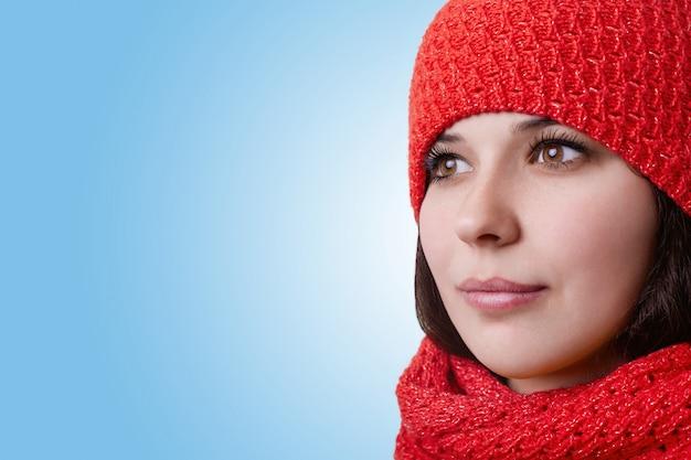 Volto di una donna attraente. bella giovane donna con grandi occhi marroni con lunghe ciglia e labbra espressive che indossa cappello rosso