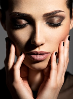Face of a beautiful girl with fashion makeup and black nails posing  over dark wall